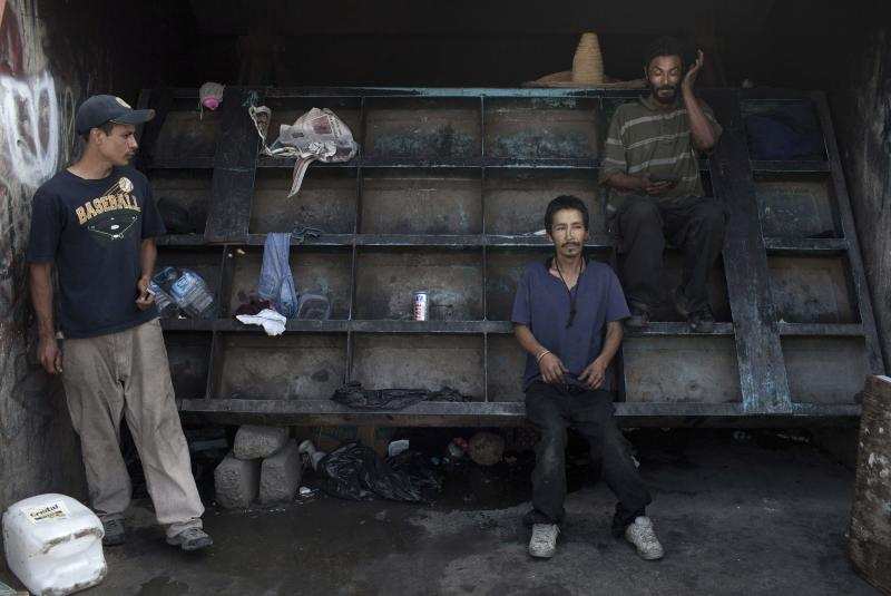 In this photo taken June 24, 2011, homeless men stand in their makeshift camp, next to a flood gate of a Tijuana River canal, in Tijuana, Mexico. During the day, deportees who find themselves in Tijuana look for work and flee Mexican police, who will jail them for not having papers, just like in the U.S. At night they take refuge in the canals, beneath bridges or in shacks made of wood, among drug addicts and people with mental health problems; a few feet from the rusty barrier that separates the country of their birth from the country where they worked years for a better life.  (AP Photo/Alejandro Cossio)
