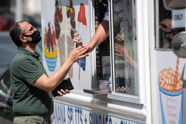A person buys a soft-serve ice cream cone at Ottawa's Commissioner's Park during the Canadian Tulip Festival May 16, 2021. (Justin Tang/Canadian Press - image credit)