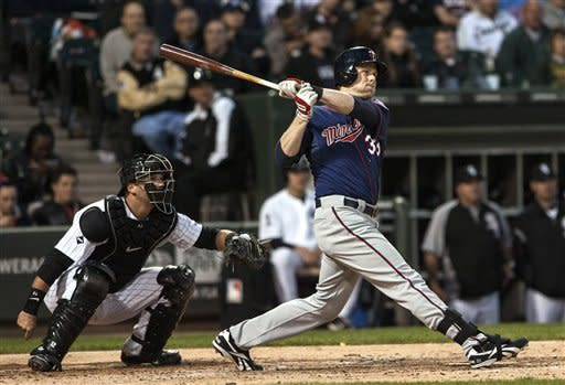 Minnesota Twins' Justin Morneau watches his three-run home run during the Twins' five-run fourth inning against the Chicago White Sox in a baseball game in Chicago on Tuesday, May 22, 2012. The White Sox catcher is A.J. Pierzynski. (AP Photo/Charles Cherney)