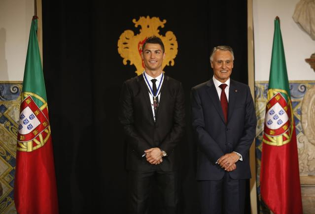 Portugal's soccer team captain Cristiano Ronaldo poses with Portugal's President Anibal Cavaco Silva (R) after receiving the Ordem do Infante Dom Henrique in Lisbon January 20, 2014. REUTERS/Rafael Marchante (PORTUGAL - Tags: SPORT SOCCER)