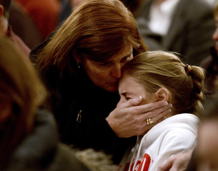 A woman comforts a young girl during a vigil service for victims of the Sandy Hook Elementary shooting, Friday, Dec. 14, 2012, at St. Rose of Lima Roman Catholic Church in Newtown, Conn. (AP Photo/Andrew Gombert, Pool)