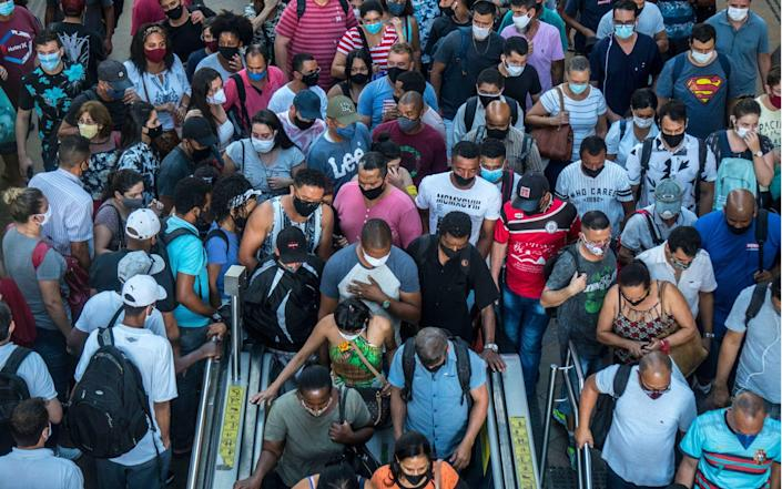 People gather to board a train at Luz station during the outbreak of the coronavirus disease - Cris Faga/Shutterstock