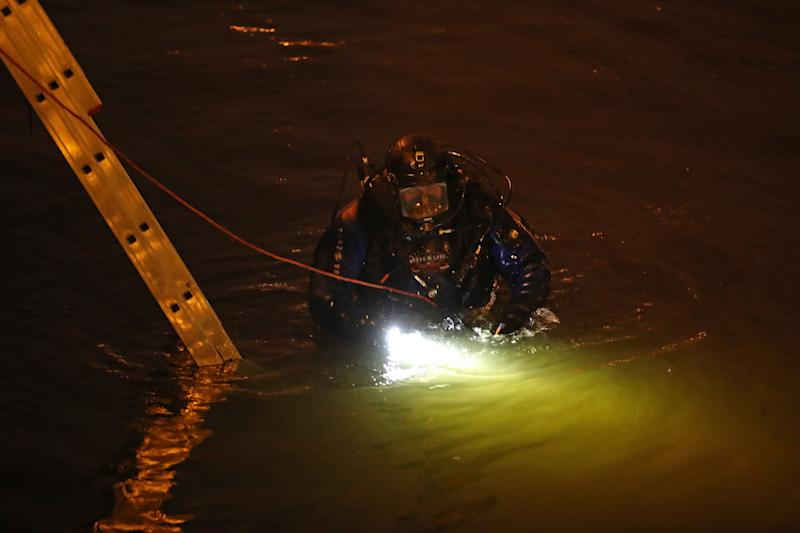 Search and rescue workers in the Moika River by an apartment block.