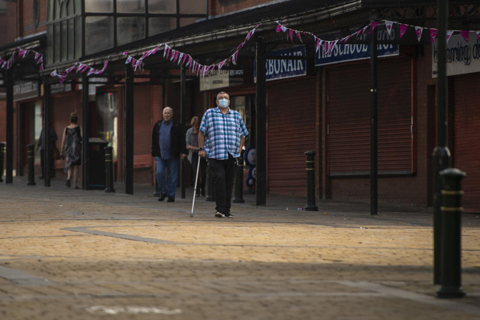 OLDHAM, ENGLAND - AUGUST 13: A man wearing a face mask walks through Oldham town centre on August 13, 2020 in Oldham, England. The town is on the brink of a local lockdown after a surge in coronavirus cases has left it the worst affected area in England. (Photo by Anthony Devlin/Getty Images)