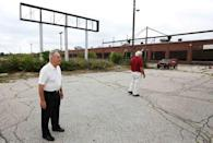 Gerald Poor (L) and long time friend and former co-worker Larry Terrell look at the now shuttered BorgWarner factory in Muncie, Indiana, U.S., August 13, 2016. Poor worked at the factory for over 40 years. REUTERS/Chris Bergin