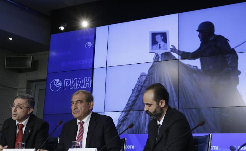 Syrian Deputy Prime Minister Qadri Jamil, center, and Minister for National Reconciliation Ali Haidar, left, speak during a news conference in Moscow, Tuesday Aug. 21, 2012. Unidentified man at right. (AP Photo/Sergey Ponomarev)