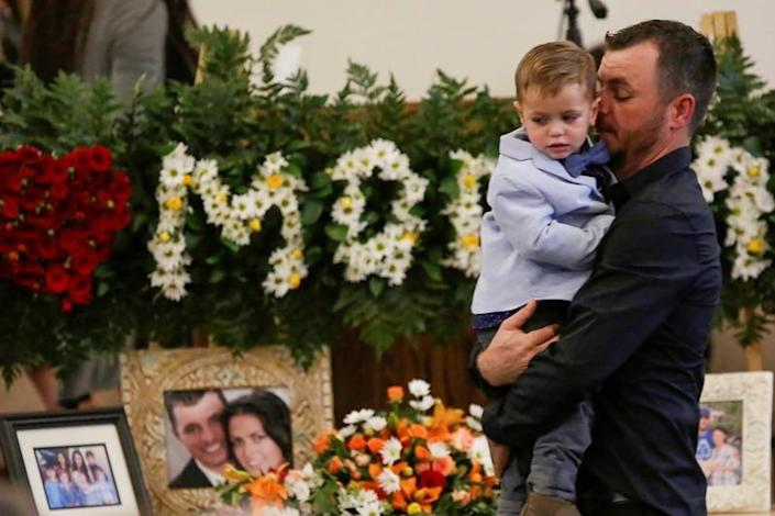 Tyler Johnson, husband of Christina Marie Langford Johnson, who was killed by unknown assailants, holds a child during her funeral service, before a burial at the cemetery in LeBaron, Chihuahua