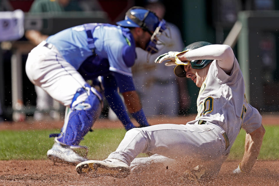 Oakland Athletics' Mark Canha slides home to score on a single by Chad Pinder during the third inning of a baseball game against the Kansas City Royals Thursday, Sept. 16, 2021, in Kansas City, Mo. (AP Photo/Charlie Riedel)