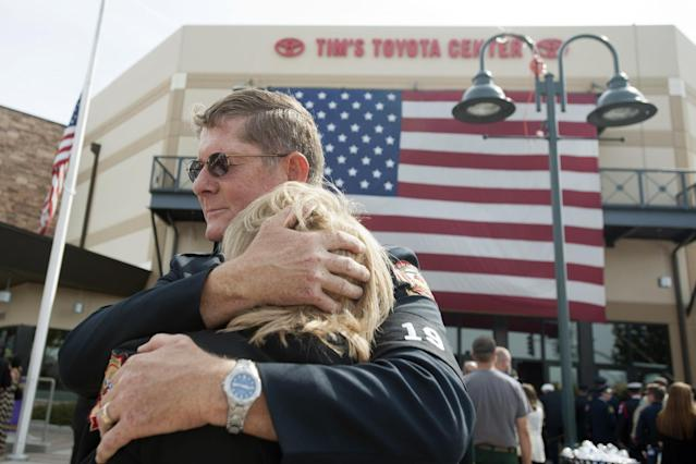 PRESCOTT VALLEY, AZ-JULY 9: Chaplain Bob Ossler with the Mayer, Arizona fire department hugs Mary Dalton, assistant chief of the Sun City West Fire Department, at the entrance to a memorial service honoring the 19 firefighters killed in a wildfire at Tim's Toyota Center July 9, 2013 in Prescott Valley, Arizona. The firefighters, of the Granite Mountain Hotshots crew, died battling the fast-moving blaze on June 30. (Photo by Laura Segall/Getty Images)