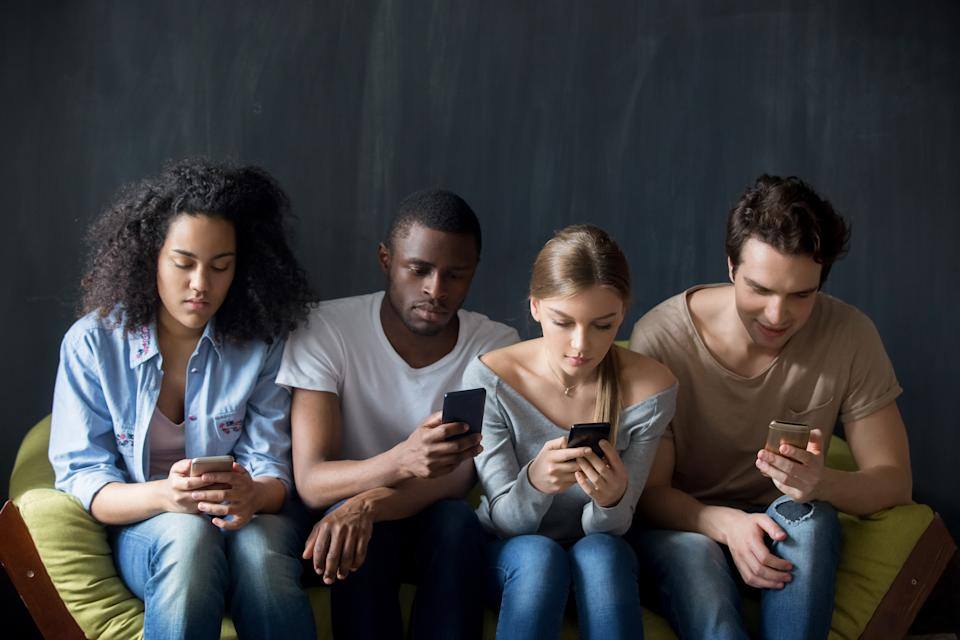 Young serious addicted to technology mixed race people sitting on couch in row, ignoring each other, using applications in smartphones, surfing websites, typing messages, scrolling social networks.