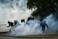 Tear gas rises around demonstrators as they clash with riot police in Cali, Colombia on May 22, 2021