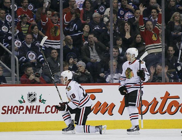 Chicago Blackhawks' Jonathan Toews (19) and Patrick Kane (88) celebrate Toews' goal against the Winnipeg Jets during the second period of an NHL hockey game in Winnipeg, Manitoba on Thursday, Nov. 21, 2013. (AP Photo/The Canadian Press, John Woods)