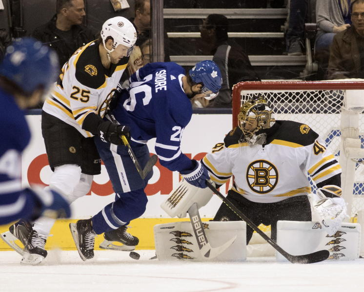 Boston Bruins goaltender Jaroslav Halak (41) keeps his eye on the action as teammate Brandon Carlo (25) takes Toronto Maple Leafs centre Nicholas Shore (26) off the puck during first period NHL hockey action in Toronto, Saturday, Oct. 19, 2019. (Fred Thornhill/The Canadian Press via AP)