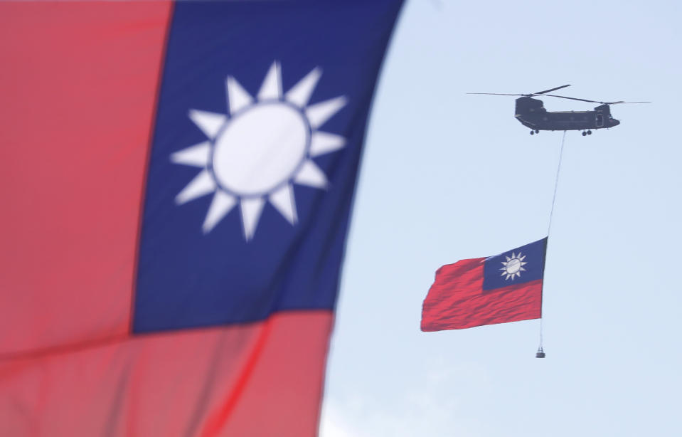 Helicopters fly over President Office with Taiwan National flag during National Day celebrations in front of the Presidential Building in Taipei, Taiwan, Sunday, Oct. 10, 2021. (AP Photo/Chiang Ying-ying)