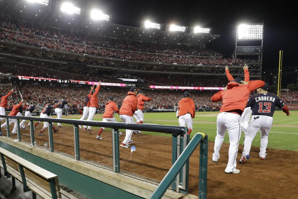 Washington Nationals players celebrate after Game 4 of the baseball National League Championship Series against the St. Louis Cardinals Tuesday, Oct. 15, 2019, in Washington. The Nationals won 7-4 to win the series 4-0. (AP Photo/Jeff Roberson)