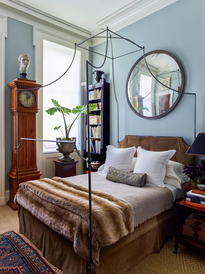"""<div class=""""caption""""> Schafer designed the custom canopy bed in the main suite in the style of a 19th-century campaign bed and had the headboard and bed skirt covered in suede by <a href=""""https://dualoy.com/"""" rel=""""nofollow noopener"""" target=""""_blank"""" data-ylk=""""slk:Dualoy"""" class=""""link rapid-noclick-resp"""">Dualoy</a>; the faux fur throw is from <a href=""""https://krbnyc.com/"""" rel=""""nofollow noopener"""" target=""""_blank"""" data-ylk=""""slk:KRB"""" class=""""link rapid-noclick-resp"""">KRB</a>, and the wool throw is from <a href=""""https://www.aerostudios.com/"""" rel=""""nofollow noopener"""" target=""""_blank"""" data-ylk=""""slk:Aero"""" class=""""link rapid-noclick-resp"""">Aero</a>. He also custom designed the ebonized bookcase in the corner. The antique mirror was purchased at <a href=""""https://www.decorativefair.com/exhibitor/nadin-mackintosh/"""" rel=""""nofollow noopener"""" target=""""_blank"""" data-ylk=""""slk:Nadin & Macintosh"""" class=""""link rapid-noclick-resp"""">Nadin & Macintosh</a>, the Swedish case clock is from <a href=""""http://www.evergreenantiques.com/"""" rel=""""nofollow noopener"""" target=""""_blank"""" data-ylk=""""slk:Evergreen Antiques"""" class=""""link rapid-noclick-resp"""">Evergreen Antiques</a>, and the cast-iron urn was bought on a trip to London and placed atop a Regency mahogany pedestal from Cove Landing. </div>"""