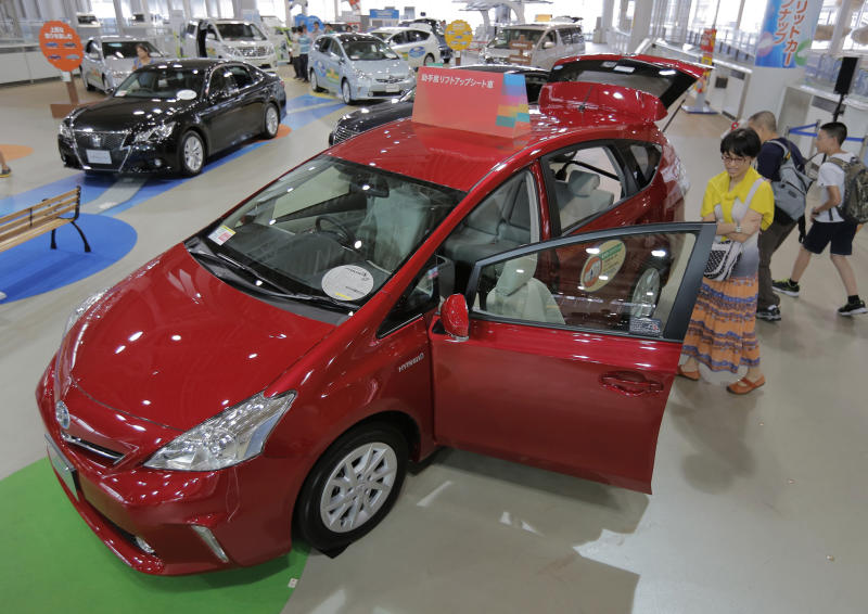Visitors look at a Prius hybrid vehicle displayed at Toyota Motor Corp.'s showroom Toyota Mega Web in Tokyo Friday, Aug. 2, 2013. Toyota nearly doubled its April-June profit from a year ago to 562.1 billion yen ($5.5 billion), getting a big boost from a cheap yen. (AP Photo/Itsuo Inouye)