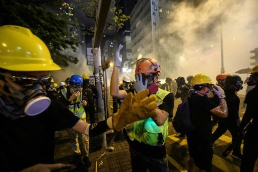 Picture taken on August 3, 2019 shows Nok (C), a volunteer medic, reacting as tear gas is fired towards protesters in the Tsim Sha Tsui area of Hong Kong's Kowloon district