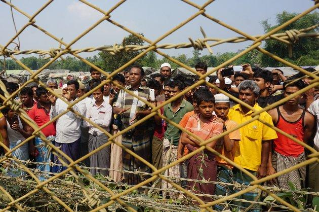 Rohingya Muslims gather behind Myanmar's border lined with barbed wire fences in Maungdaw district, located in Rakhine State bounded by Bangladesh on March 18, 2018.