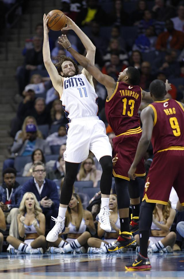 Charlotte Bobcats forward Josh McRoberts, left, pulls down an offensive rebound against Cleveland Cavaliers forward Tristan Thompson as Cavaliers forward Luol Deng watches during the first half of an NBA basketball game in Charlotte, N.C., Friday, March 7, 2014. (AP Photo/Nell Redmond)