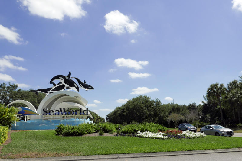Cars pass by the entrance to the SeaWorld Theme park as it remains closed Monday, March 30, 2020, in Orlando, Fla. SeaWorld is indefinitely furloughing more than 90% of its employees and they won't get paid after March 31. (AP Photo/John Raoux)