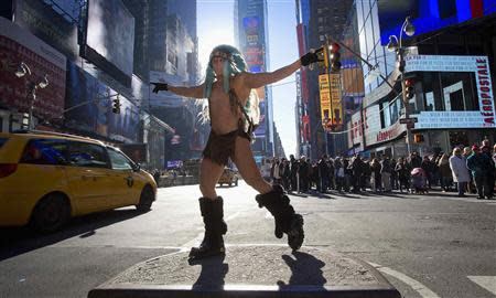 """Adam David poses for tips as """"The Naked Indian"""" as people walk past in Times Square in New York, December 28, 2013. REUTERS/Carlo Allegri"""