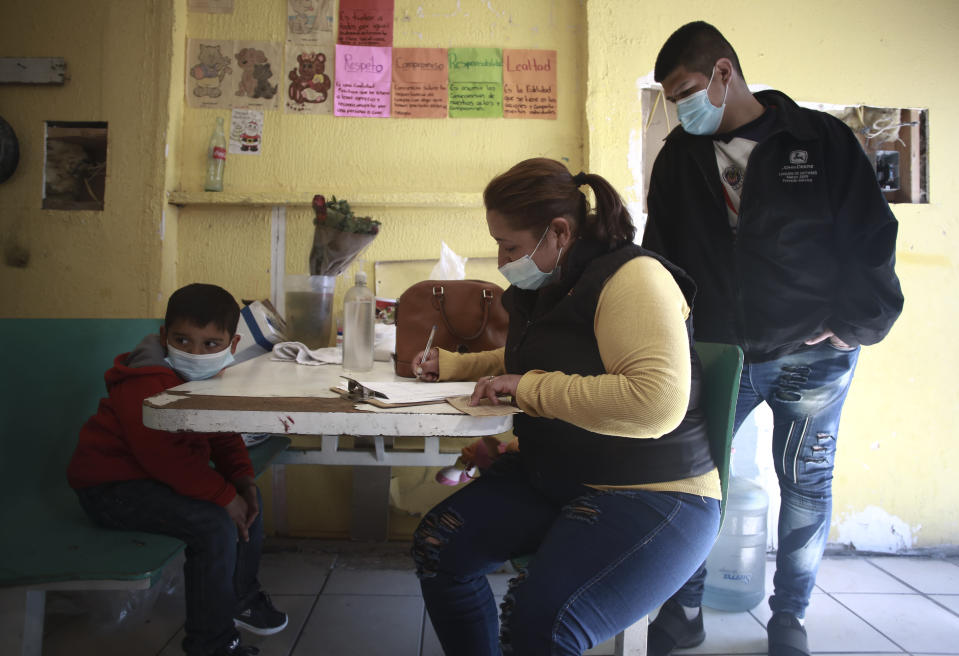 An Honduran migrant registers at the Pan de Vida shelter manager in Ciudad Juarez, Mexico, Friday, Feb. 19, 2021. After waiting months and sometimes years in Mexico, people seeking asylum in the United States are being allowed into the country starting Friday as they wait for courts to decide on their cases, unwinding one of the Trump administration's signature immigration policies that President Joe Biden vowed to end. (AP Photo/Christian Chavez)