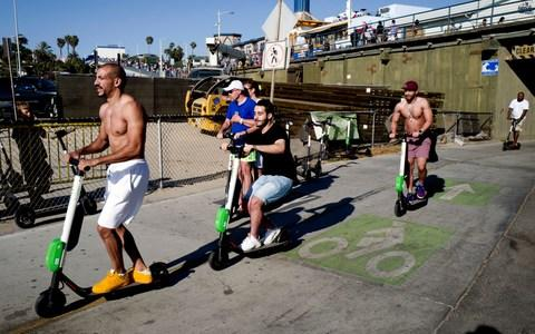 People ride Lime and Bird scooters along the strand in Santa Monica, California - Credit: Richard Vogel/AP