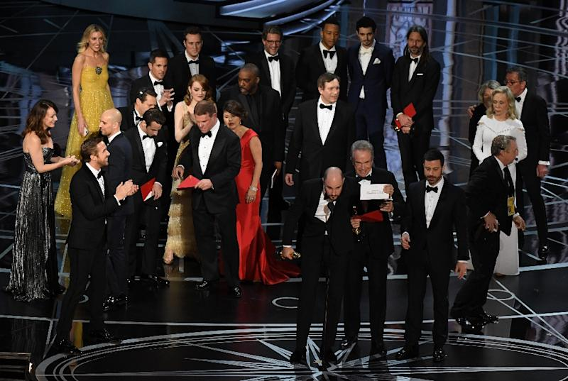 """""""La La Land"""" producer Jordan Horowitz (front C) shows the card saying """"Moonlight"""" won the best picture on February 26, 2017 in Hollywood, California"""