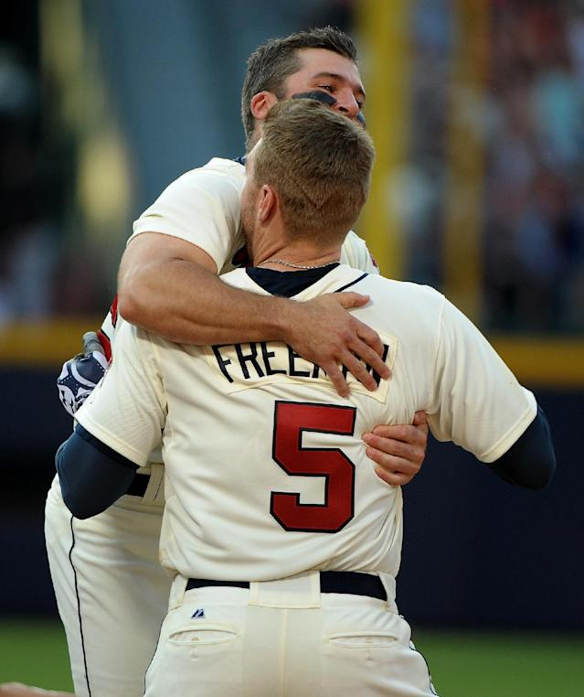 Atlanta Braves' Freddie Freeman is congratulated by teammate Dan Uggla after Freeman's bases loaded single scores the winning run during the ninth inning of their baseball game against the San Francisco Giants at Turner Field, Saturday, June 15, 2013, in Atlanta. The Braves won 6-5. (AP Photo/David Tulis)