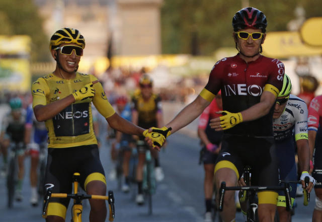 FILE - In this Sunday, July 28, 2019 file photo, Colombia's Egan Bernal wearing the overall leader's yellow jersey, left, holds hands with Britain's Geraint Thomas after winning the Tour de France cycling race in Paris. The team of reigning Tour de France champion Egan Bernal has withdrawn from all races over the next three weeks amid the spread of the new virus outbreak and following the death of one of its sports directors. (AP Photo/Michel Euler, File)