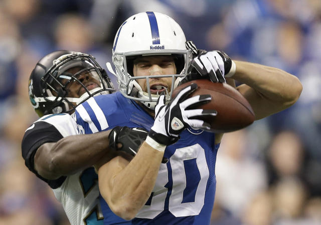 Indianapolis Colts' Coby Fleener (80) is defended by Jacksonville Jaguars' Johnathan Cyprien during the first half of an NFL football game on Sunday, Dec. 29, 2013, in Indianapolis. (AP Photo/Michael Conroy)