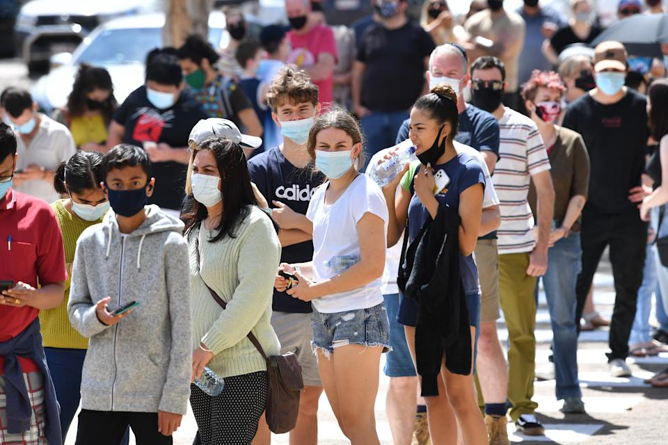 People are seen lined up to receive a vaccination for COVID-19 at the Boondall mass vaccination hub in Brisbane. Source: AAP