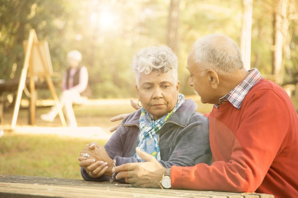 Mixed race senior adult couple talk at outdoor park in spring or autumn season. They sit on a park bench and discuss their relationship difficulties. African and middle eastern descent couple. Woman painting using easel in background.