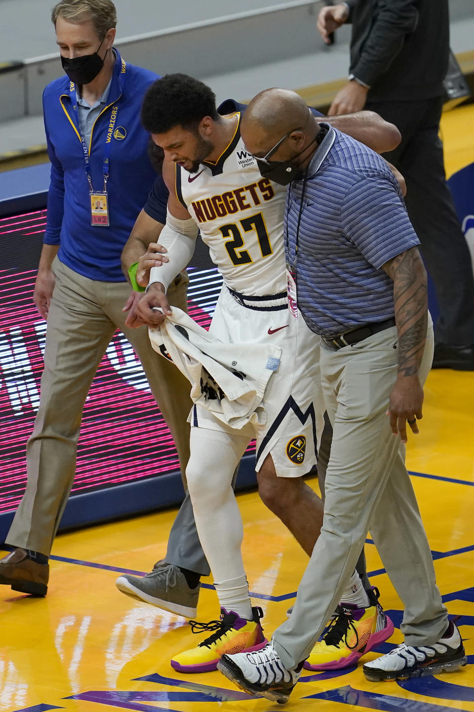 Denver Nuggets guard Jamal Murray (27) is helped off the floor during the second half of an NBA basketball game against the Golden State Warriors in San Francisco, Monday, April 12, 2021. (AP Photo/Jeff Chiu)