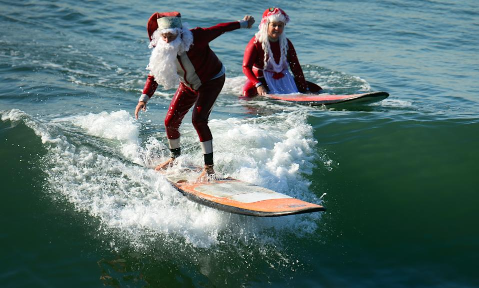 Surfing Santa, Michael Pless, 62, (L) catches a wave as his wife Jill watches, at Seal Beach , south of Los Angeles, on December 21, 2012 in California. Pless, who runs a surfing school, has been dressing up as Santa Claus and taking to the waves in costume since the 1990s.  AFP PHOTO / Frederic J. BROWNFrederic J. BROWN        (Photo credit should read FREDERIC J. BROWN/AFP/Getty Images)
