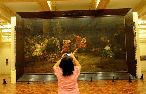 "A tourist takes a photograph of the restored painting ""Spoliarium"", at the National Museum in Manila"