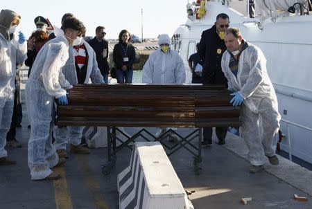 A coffin containing the body of a migrant who died, is carried off a navy ship at the Sicilian harbour of Empedocle December 5, 2014. REUTERS/Antonio Parrinello