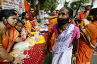 Volunteers of an organization distribute gifts to economically underprivileged people ahead of Durga Puja, the biggest festival of the region, in Kolkata, India, Wednesday, Oct. 21, 2020. Health officials have warned about the potential for the coronavirus to spread during the upcoming religious festival season, which is marked by huge gatherings in temples and shopping districts. Durga Puja, the biggest festival in the region, will be celebrated from Oct. 22-26. (AP Photo/Bikas Das)