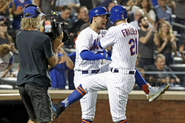 New York Mets' J.D. Davis celebrates with Todd Frazier, right, after scoring on Frazier's two-run home run during the first inning of the team's baseball game against the Arizona Diamondbacks, Wednesday, Sept. 11, 2019, in New York. (AP Photo/Kathy Willens)