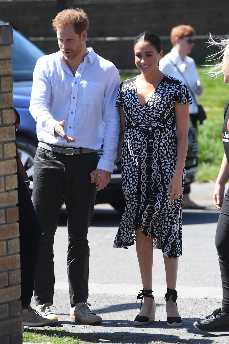 """The Duchess arrived at her first engagement in Cape Town with Prince Harry wearing a £69 monochrome wrap dress by Mayamiko, a sustainable and ethical African label. The sold-out dress is made using traditional African techniques and locally-printed fabrics. A pair of black canvas wedge espadrilles by Castaner completed the look. The shoes are available to purchase for £80. <a href=""""https://fave.co/2m777eL"""" rel=""""nofollow noopener"""" target=""""_blank"""" data-ylk=""""slk:Shop now"""" class=""""link rapid-noclick-resp""""><strong>Shop now</strong></a><strong>. </strong><em>[Photo: Getty Images]</em>"""