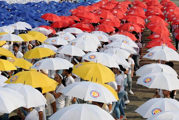 Students holding umbrellas rehearse a dance hours prior to the arrival of Pope Francis at a military airbase in Manila on January 15, 2015