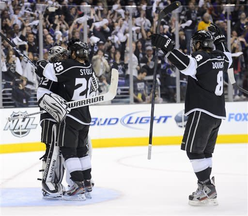 Los Angeles Kings goalie Jonathan Quick, left, Jarret Stoll, center, and Drew Doughty celebrate their 2-1 win against the Phoenix Coyotes during Game 3 of the NHL hockey Stanley Cup Western Conference finals, Thursday, May 17, 2012, in Los Angeles. The Kings won 2-1. (AP Photo/Mark J. Terrill)