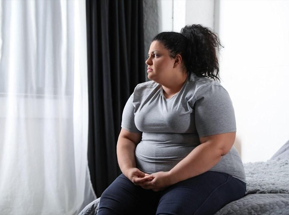 Depressed overweight woman on bed at home