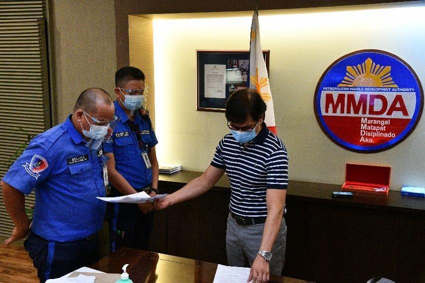 MMDA Chairman Benhur Abalos serves respective notices to the two traffic enforcers being investigated