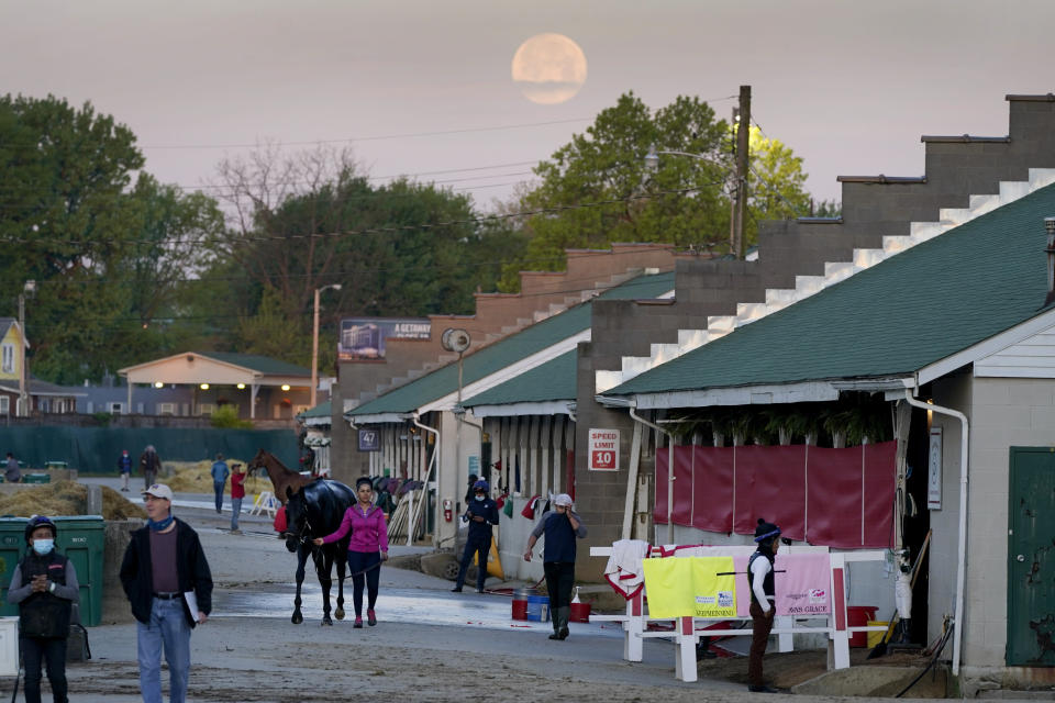 Workers tend to horses in barns as the full moon sets during morning workouts at Churchill Downs Tuesday, April 27, 2021, in Louisville, Ky. The 147th running of the Kentucky Derby is scheduled for Saturday, May 1. (AP Photo/Charlie Riedel)