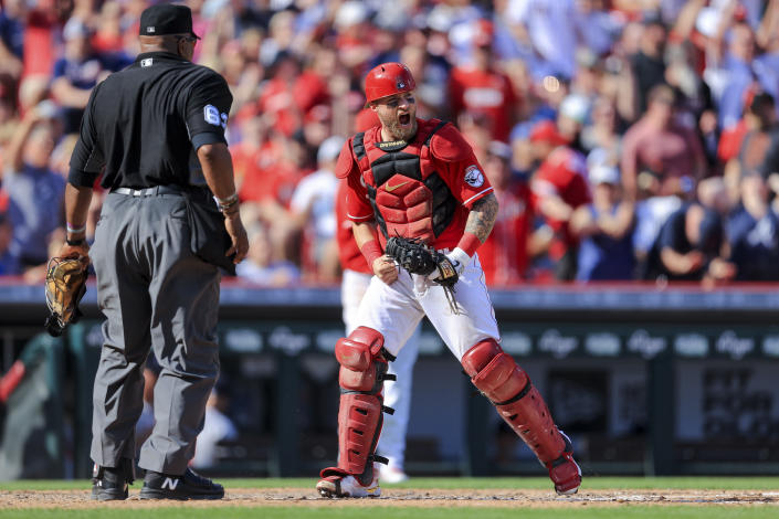 Cincinnati Reds' Tucker Barnhart, right, reacts after tagging out Atlanta Braves' Guillermo Heredia at home plate to end the sixth inning of a baseball game in Cincinnati, Saturday, June 26, 2021. (AP Photo/Aaron Doster)