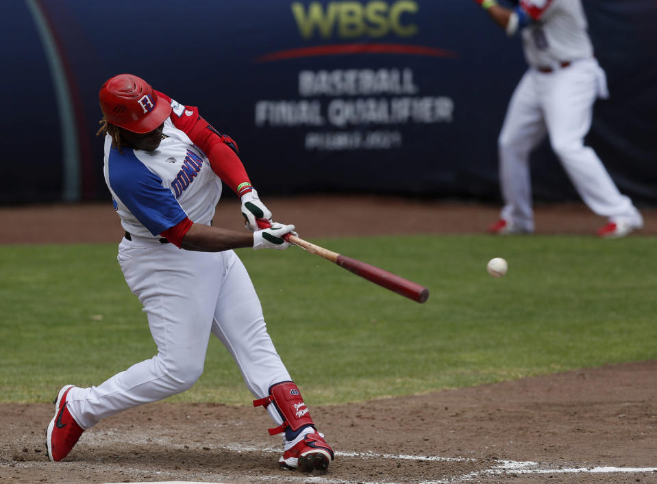 Dominican Republic outfielder Johan Mieses connects a single against Venezuela during a final Olympic baseball qualifier game, in Puebla, Mexico, Saturday, June 26, 2021. (AP Photo/Fernando Llano)