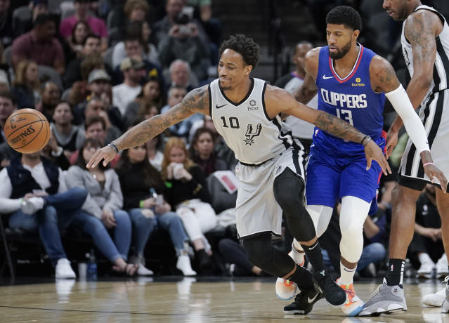 San Antonio Spurs' DeMar DeRozan (10) and Los Angeles Clippers' Paul George chase the ball during the first half of an NBA basketball game, Saturday, Dec. 21, 2019, in San Antonio. (AP Photo/Darren Abate)