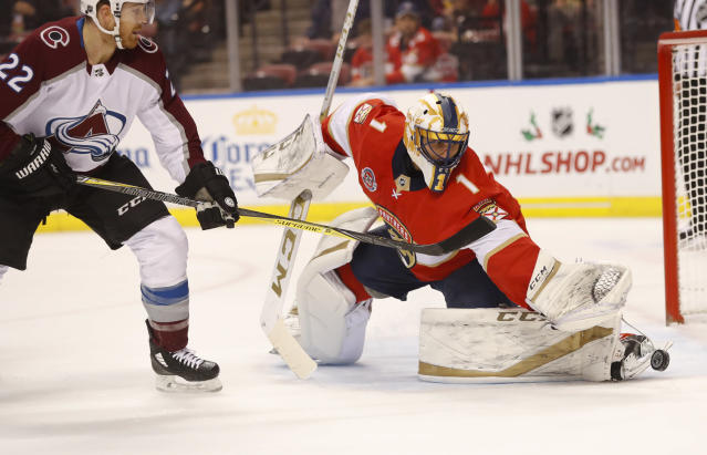 Florida Panthers goaltender Roberto Luongo (1) deflects a shot as Colorado Avalanche center Colin Wilson (22) looks on during the first period of an NHL hockey game, Thursday, Dec. 6, 2018, in Sunrise, Fla. (AP Photo/Wilfredo Lee)